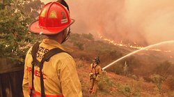 The number of wildfires in San Diego is expected to increase as a result of climate change. In this photo, a San Diego firefighter battles flames in Tierrasanta during 2003 wildfires.