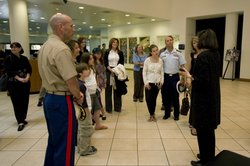 Local military families tour the Museum of Photographic Arts with Executive Director Deborah Klochko.