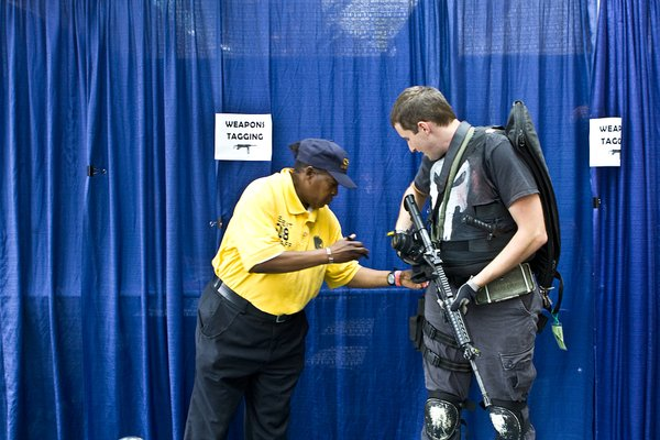 A Comic-Con attendee's fake weapons are inspected and tagged as safe before he can go on to the convention floor.