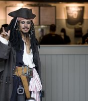 A Comic-Con cosplayer dressed as Jack Sparrow breaks for a coffee.