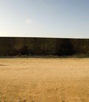 A man walks along a rusty segment of the fence on the Mexican side. Many migrants travel north through Mexico with hopes of crossing the border, but settle in Tijuana because of the difficulty associated with the crossing.