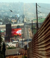 The border fence extends west across the hills toward the ocean. Tijuana's urban development is dense near the border.
