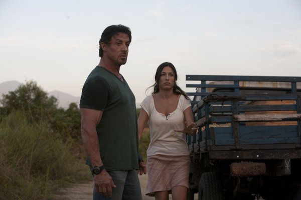Sylvester Stallone and one of the rare female presences in the film, Giselle Iti.