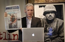 Julian Assange of the WikiLeaks website holds up a copy of The Guardian newspaper as he speaks to reporters in front of a Don McCullin Vietnam war photograph at The Front Line Club on July 26, 2010 in London, England.