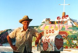 Salton Sea resident Leonard Knight next to his Salvation Mountain built out of mud and paint.