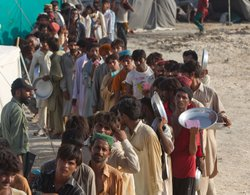 Flood victims line up for food distribution at a tented camp on August 21, 2010 in Sukkur , Pakistan. The country's agricultural heartland has been devastated, with rice, corn and wheat crops destroyed by floods.
