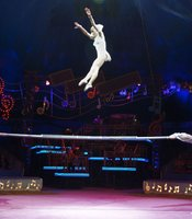 "The Rodion Trio performs on the Russian barre. Big Apple Circus Founder Paul Binder features the Rodion Trio, an act he's wanted to acquire since he saw them perform in Europe years before. ""The Rodion Trio connects beautifully with the audience,"" says Binder. ""Anna, the flyer, is extraordinary; one in a million. She has a sixth sense and she moves through the air making tricks like a triple and a double somersault with a twist, as if she's found rails in the air on which to ride,"" he says."