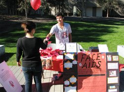 A volunteer at UCSD hands a student a condom rose in honor of World AIDS Day. Health officials say young adults, especially minorities, are at risk for HIV infection.