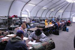 Homeless vets sign in and dress their bunks as the San Diego Veterans Winter Shelter opens in the Midway district.