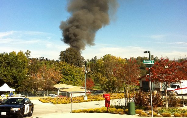 Smoke is seen in Escondido as authorities set fire to a home they said was so packed with homemade explosives that they had no choice but to burn it to the ground.