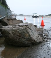 A rock slide slows traffic on Navajo Road in the San Carlos neighborhood of San Diego.  