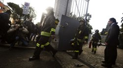 Italian carabinieri and firemen leave the Swiss Embassy in Rome on Thursday after a parcel bomb exploded.
