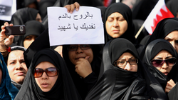 "A Bahraini Shiite woman holds a sign with the words ""We sacrifice our souls and blood for martyrs"" written in Arabic during a funeral for men killed the day before during a violent police raid in Manama."