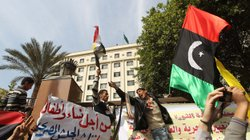 Protesters shout slogans against Libyan leader Moamer Kadhafi as they hold up the old Libya flag during a demonstration Tuesday outside the Arab League headquarters in Cairo.