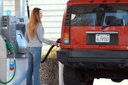 A woman pumps gasoline into her Hummer at a chevron service station in San Rafael, California. 