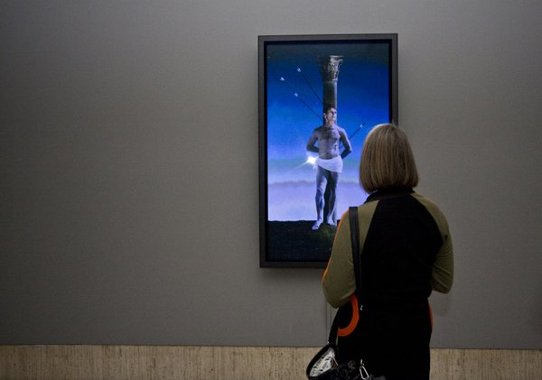 A visitor to the Timken Museum of Art takes in artist Robert Wilson's video portrait of Mikhail Baryshnikov as Saint Sebastian, shot with arrows.