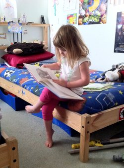 Four-year-old Gabriella Anderson spends her free time reading a hardback book in her brothers&#39; bedroom.  