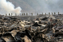 Japanese military members walk through devastation to search for missing people at Otsuchi town in Iwate prefecture on March 13, 2011. 