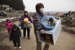 The Sasaki family carry some of their personal belongings from their home that was destroyed after the devastating earthquake and tsunami on March 15, 2011 in Rikuzentakata, Miyagi province, Japan.