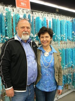 Shlomo and Pnina Gruer in front of a wall of beads.