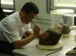 Mr. Zhou Tie is cleaning a Terracotta Warrior head.