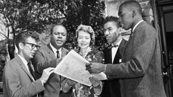 "Members of the Congress of Racial Equality (CORE) in Washington, DC as they prepare for their journey south. Left to right: Edward Blankenheim, James Farmer (Co-founder and National Director of CORE), Genevieve Hughes Houghton, the Reverend B. Elton Cox and Henry ""Hank"" Thomas."