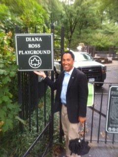 Councilman Todd Gloria stands next to a sign recognizing a private donation in New York City's Central Park. Gloria said similar sponsorships could be used in Balboa Park.