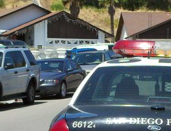 A San Diego police car sits outside of a house Bay Terraces where a family of four was found dead in and around the house on May 24, 2011.