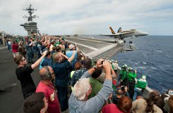 Sailors friends and family watch an F/A-18C Hornet, assigned to Strike Fighter Squadron (VFA) 25 launch from the flight deck of the Nimitz-class aircraft carrier USS Carl Vinson (CVN 70) during the ship&#39;s Tiger Cruise air show. Carl Vinson and Carrier Air Wing (CVW) 17 recently completed a deployment the U.S. 5th Fleet and U.S. 7th Fleet areas of responsibility, June 11, 2011.