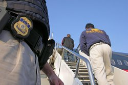 An ICE officer stands guard while deportees board a plane headed to their home country.
