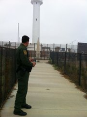 A Border Patrol agent stands in front of the historic marker between Tijuana and Imperial Beach, the morning after a confrontation between agents and migrants crossing illegally led to a Mexican man's death just a few miles from here.