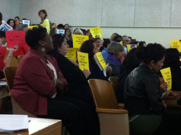 Teachers, parents, students and administrators have testified at Board of Education meetings since March about how budget cuts will hurt their schools. Some held up signs asking for restoration of the district&#39;s Community-Based English Tutoring program at a meeting earlier this year.