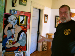John Keasler shows off one of his paintings in his North Park home. Keasler was diagnosed with HIV in 1988. He saw many of his friends die of AIDS.