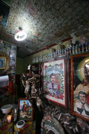Money given in thanks to Malverde adorns the walls and ceiling of one room.