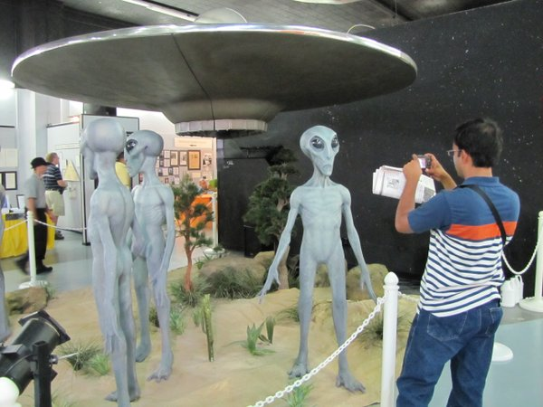 A terrestrial visitor takes in an exhibit of an extraterrestrial visitors at the Roswell UFO Museum.