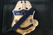 A Border Patrol agent wears a black band over his badge to honor slain Agent Brian Terry.