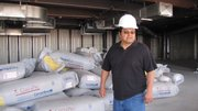 Hualapai Tribal Council member Waylon Honga stands in front of bags of insulation that have yet to be installed in the unfinished visitor center.