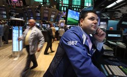 Traders work on the floor of the New York Stock Exchange before the opening bell on August 5, 2011 in New York City.