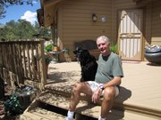 Larry Prochnau sits in front of his home in Prescott next to his dog Jake. Larry and his wife have been able to retire on state pensions.