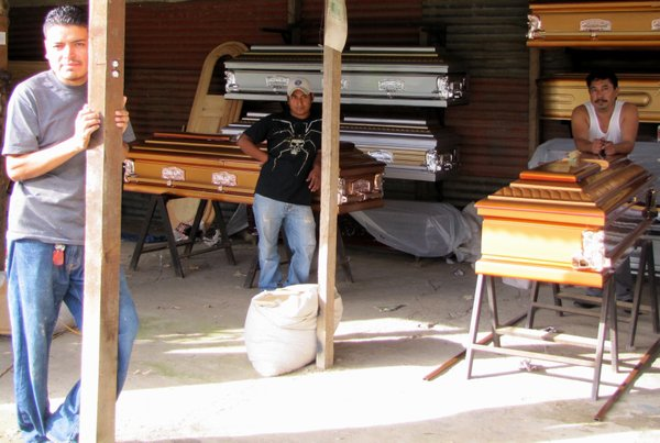 Three Guatemalan coffin builders, who make $7 a day, debate the risk of moving to the United States illegally. Marvin Gomez (far left)  was deported after spending five months in an American prison. Jose Rodas (middle) is considering the voyage north. Americo Barahona says it's not worth the risk.