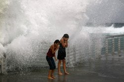 Lilyana Fowler (L) and Isabella Lugli brace themselves as a wave bursts onto a pier at the Boynton Beach inlet on August 25, 2011 in Boynton Beach, Florida. 
