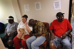 Amy Smith (2nd L) waits to apply for food stamps at the Cooperative Feeding Program as she sits with Theordore Adams (2nd R)) and Ron Sanders (R) both of whom are already in the federal food stamps program on February 10, 2011 in Fort Lauderdale, Florida.