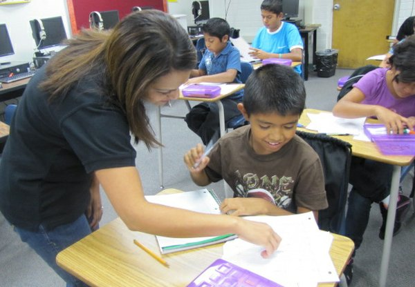 Teacher Annie Bhatnager helps a student with an assignment in the Newcomer class during the first week of school.