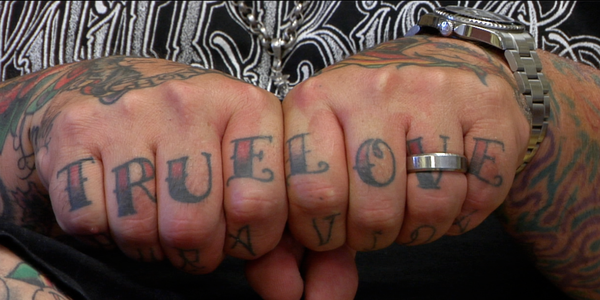 "The hands of tattoo artist Chris Winn, curator of ""Inspired by Ink."""