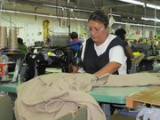 Diana Sosa helps make a flame-retardant protective suit at the Neese de México factory in Piedras Negras, Mexico.