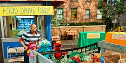 "Chris, Elmo, Rosita, and a new character dealing with hunger, Lily, load food into the truck to donate to the food bank as part of Sesame Street's primetime television special ""Growing Hope Against Hunger."" © 2011 Sesame Workshop."