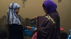Somali refugee Mana Ahmed Mohamed helps her daughter Idil Nunow wash her hands before enjoying a traditional Somali feast.