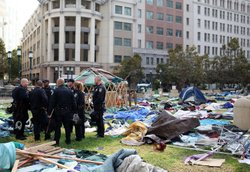 Oakland police officers stand in the remains of the Occupy Oakland camp after police shut the encampment down on October 25, 2011 in Oakland, California.