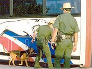 Border Patrol agents inspect the cargo area of a bus.