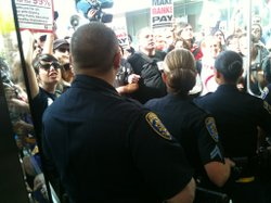 Police keep protesters outside of Cal State Trustees headquarters in Long Beach, Calif.